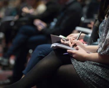 Foto por The Climate Reality Project - pessoas sentadas escrevendo em cadernos - curso de espanhol